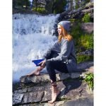Hoodie_Grey_Girl-sitting-with-notebook-by-waterfall